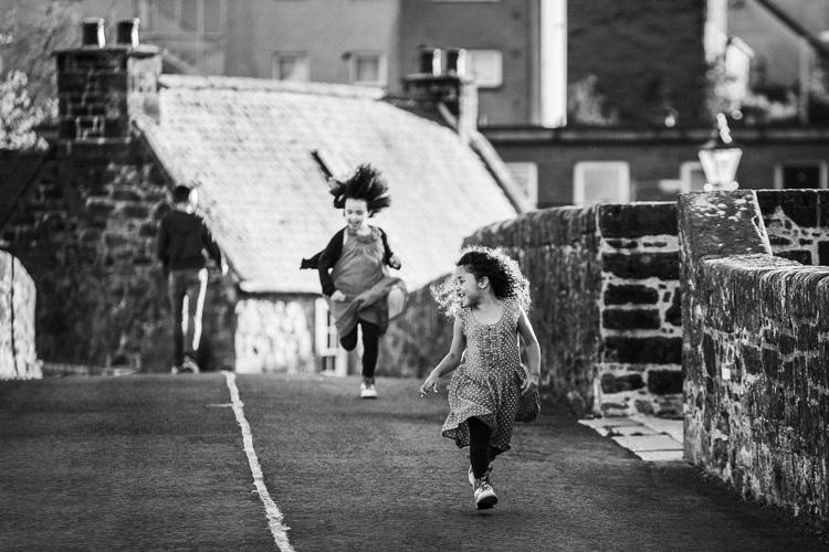 Girls running on Devorgilla Bridge in Dumfries