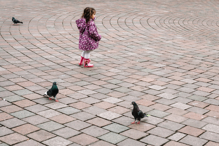 Girl running after birds on St Enoch Square