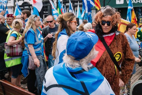 Fancy dress SNP supportes talks to the participant wrapped in St Andrews flag
