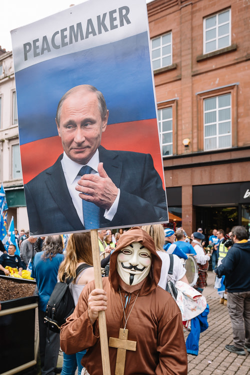 "The Anonymous member with ""Putin the Peacemaker"" sign in All Under One Banner march"