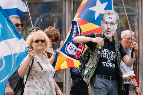 "A marcher wearing ""Never trust a Tory"" T-shirt and a mask of David Mundell, Secretary of State for Scotland, with a Yes meme on the forehead"