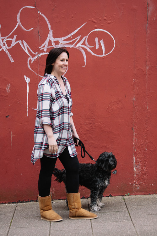 Urban shoot with Julie and her dog Toby against a red wall with graffiti scroll
