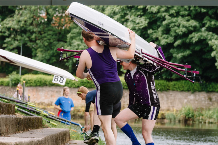 The doubles team from Aberdeen Boat Club carrying their boat away of the river