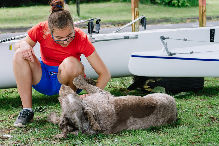 Girl rower playing with the dog in between the regatta races