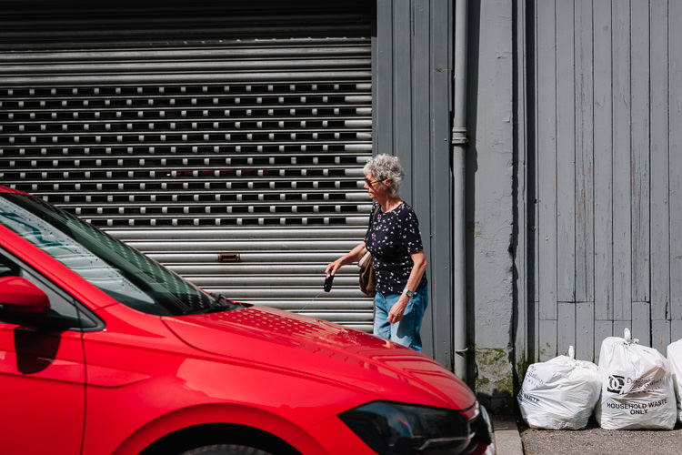 Dumfries street photographs - a woman and a passing red car on English Street