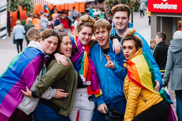 A group of young people cloaked in rainbow banners