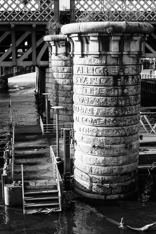 The etched granite pillars of the disused Victorian bridge