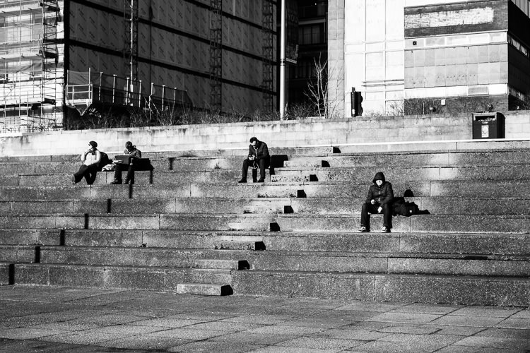 People seating in the sun on the steps leading to Clydeside walk