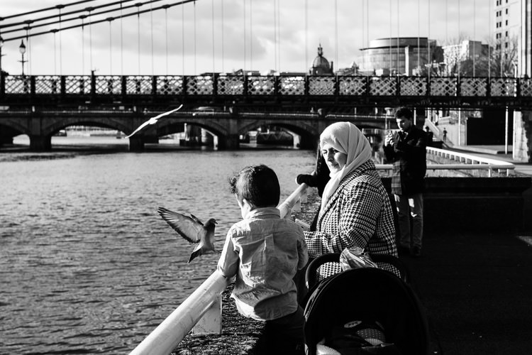 Mother and sun looking at the brave pigeon begging treats near the river Clyde in Glasgow city centre