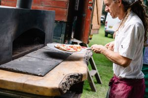 Making a pizza by Northern Wilds Wood-Fired Pizzas