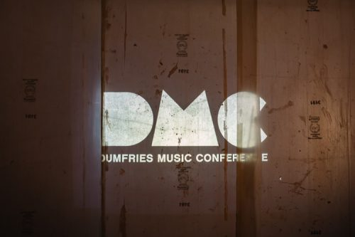Dumfries Music Conference logo projected onto the back wall of the Oven