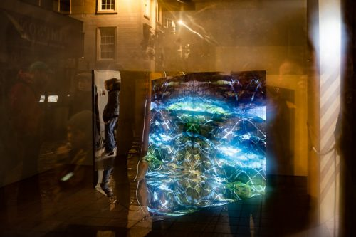 Heather Lander's sonic art piece viewed from the street, with Dumfries urban structures reflected in the window