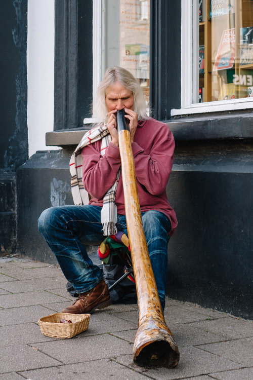 Didgeridoo player extracting a low pitch vibrating sound from his instrument