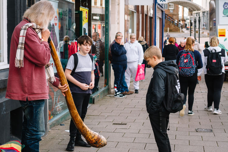 Dumfries school children stop, curious to hear the didgeridoo sound