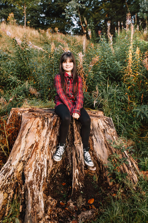 A girl on a red tartan shirt rests on a tree stump