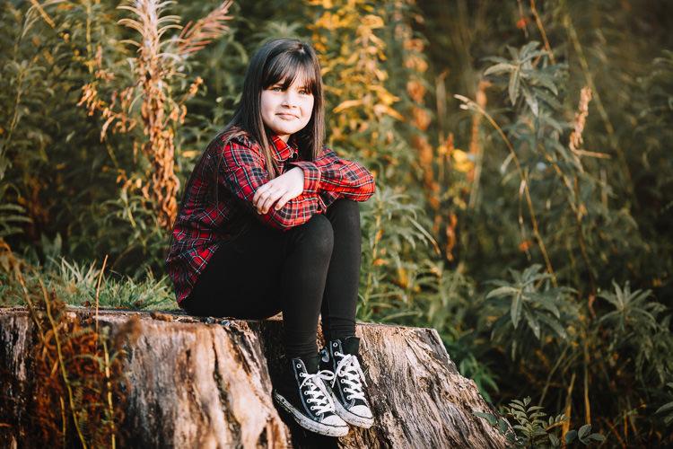Autumn portrait of a girl sitting on the tree stump