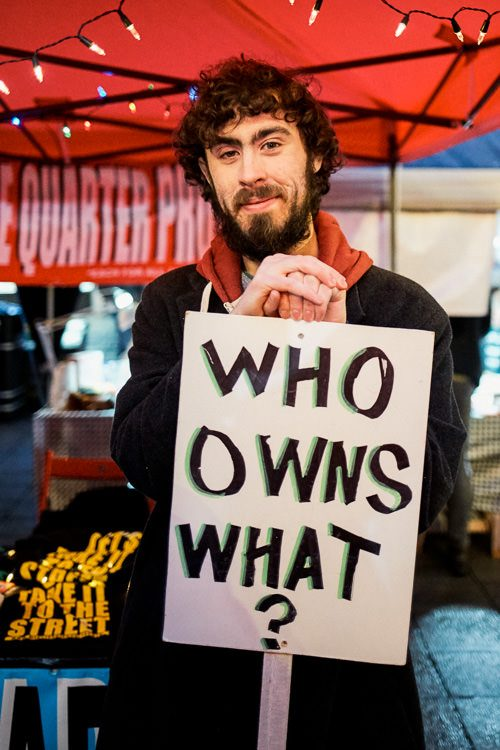 """Michael with """"Who owns what?"""" sign at MSQ stall promoting community activism"""