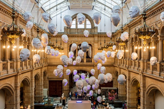 A wide view from the staircase onto Floating Heads (or Expression) installation by Sophie Cave's in Kelvingrove Art Gallery