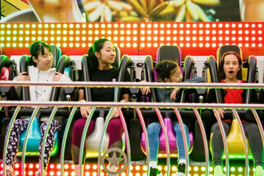 A group of teens in the air on Viva Mexico funfair ride at St Enoch Square
