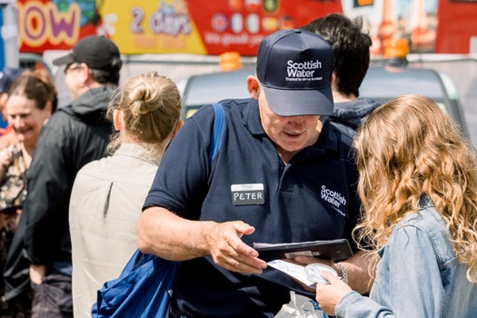 A Scottish Water staff member chats with a member of the public at George Square, Glasgow, during Your Water Your Life campaign event