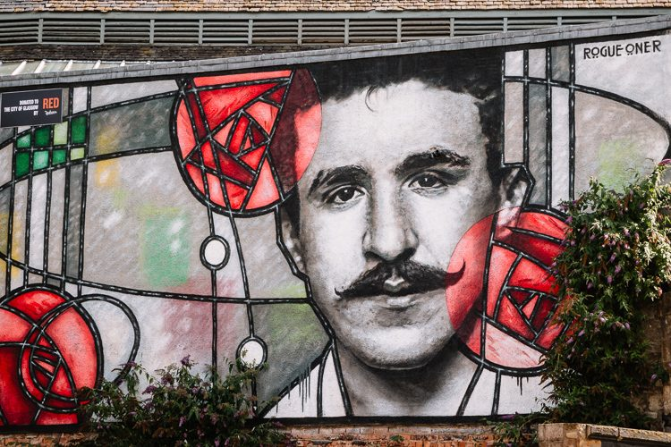 60 feet by 40 feet giant piece of street art depicting Charles Rennie Mackintosh peering through an Art Deco stained glass window