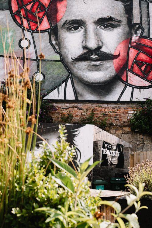 Mural through the summer greens of the Clutha beer garden