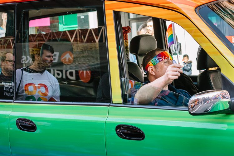 Glasgow Taxis vehicle in rainbow colours with marchers reflected in the window
