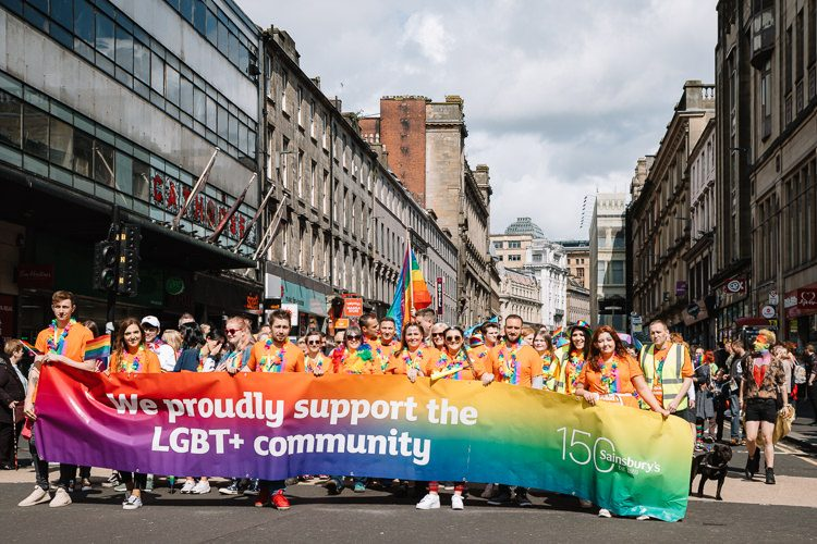 "Sainsbury workers march along Union Steet carrying ""We proudly support the LGBT+ community"" banner"