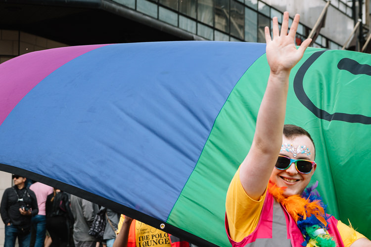 A participant of Glasgow Pride Parade greets Glaswegians lining the streets