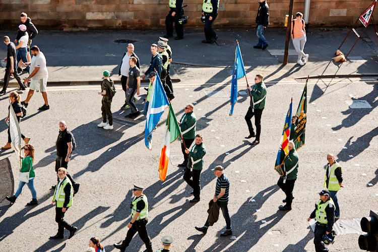 Saltire and Irish flags carried at the head of the procession returning from a ceremony held at La Passionaria statue on the Clyde bank