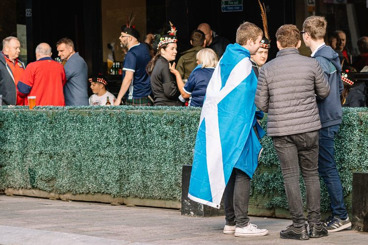 Scotland team supporter wrapped in the Saltire flag chatting with mates