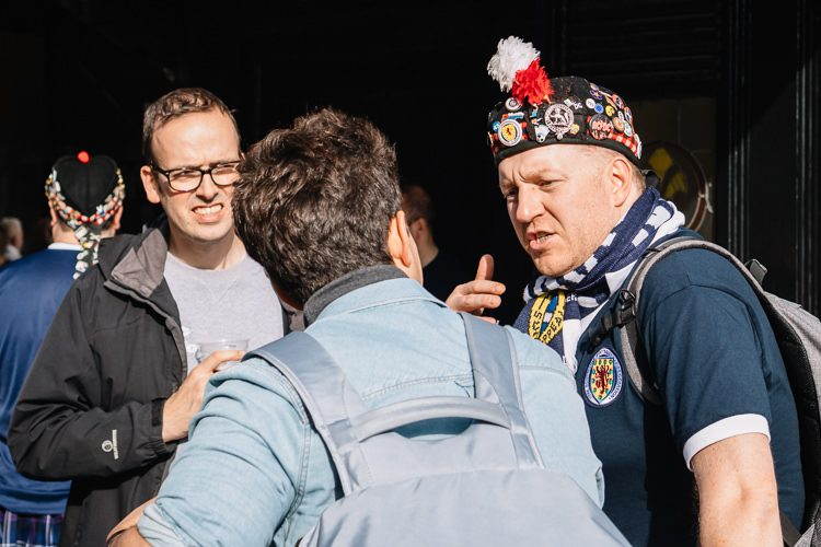 In conversation - a fan wearing a badge covered diced Glengarry hat and a T-shirt with Scotland rampant lion and eleven thistles sticker
