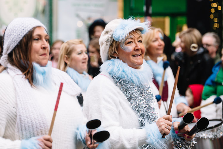 Musicians in white jumpers with silvern tinsel
