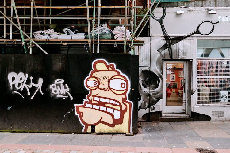 A cartoon head by Oh Pandah next to Smug's Scull and Scissors mural on the hairdresser's salon