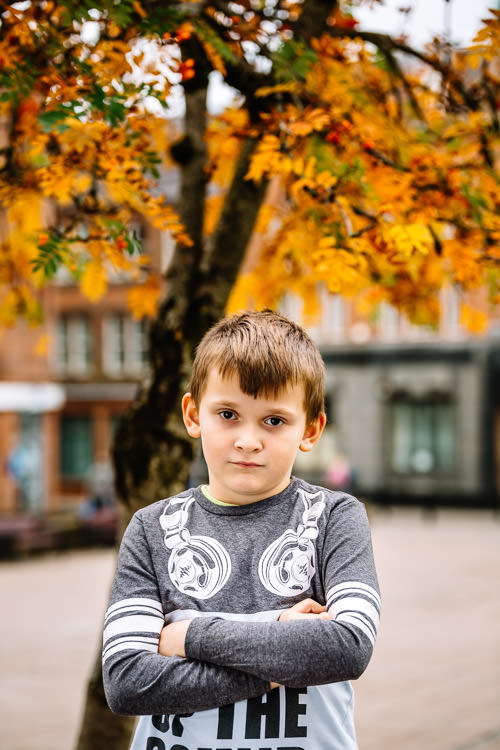 Kevin standing on the bench under a rowan tree at Queenberry Square for his urban autumn photo session