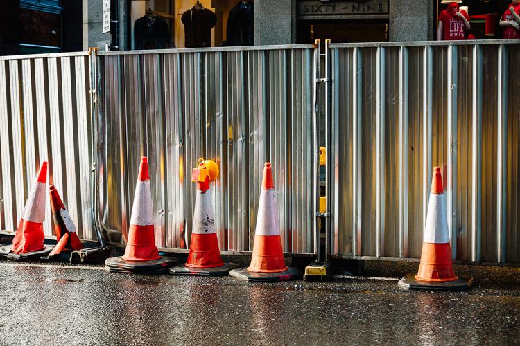 Traffic cones throwing orange patterns onto the metal fence