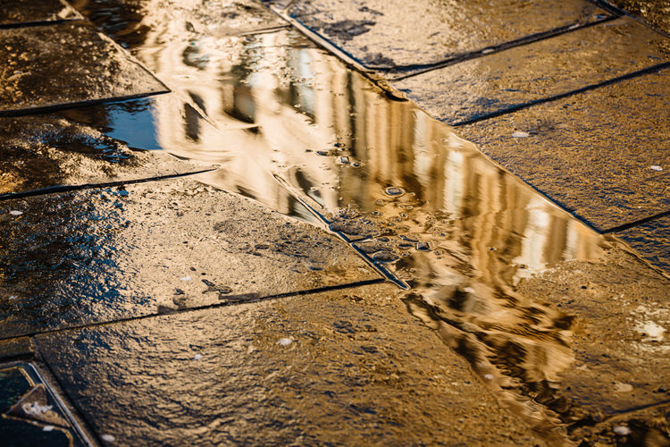 Argyle Street buildings reflected in the puddle of the melted snow