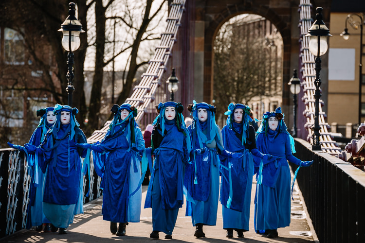 Dressed in blue robes and headdresses, the performers move solemnly and silently in support of Blue Wave demonstrators