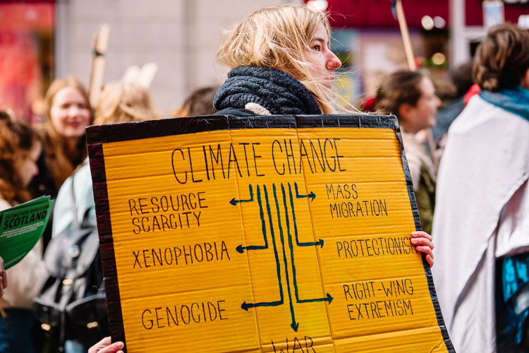 Girl carrying a yellow climate changer poster