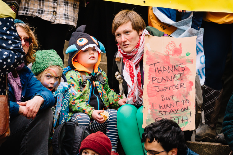 "Mum and kids sitting on the steps with ""Thanks planet Jupiter but i want to stay on Earth"" homemade poster"