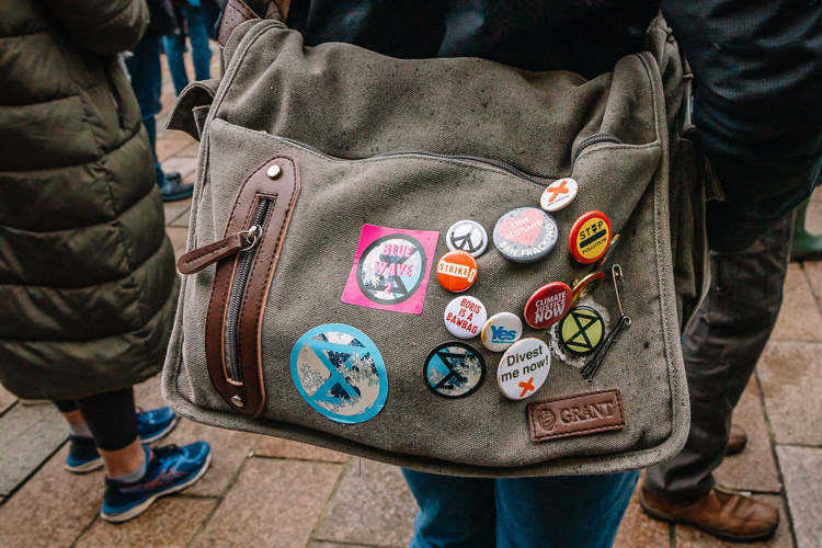 Detail - a bag with climate protest stickers and badges
