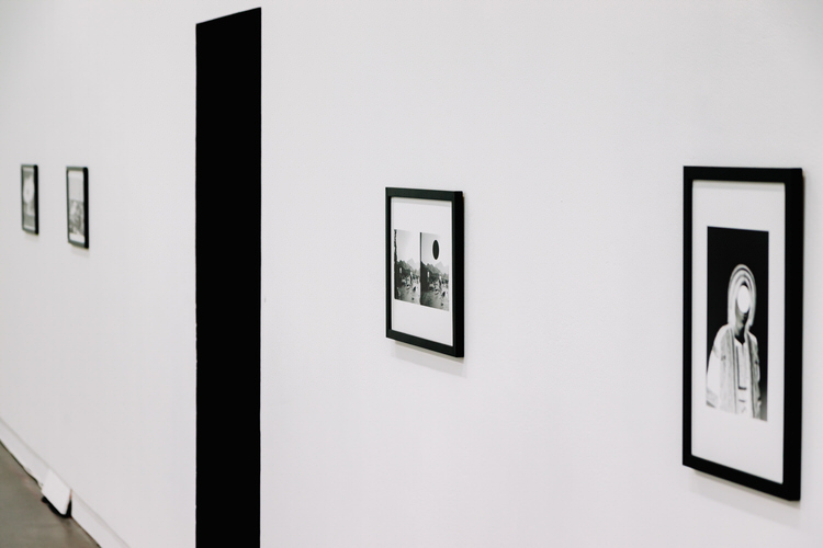A series of framed monochrome positive and negative prints sourced from digital archives, each marked by a large dot, on the walls of CCA3, the black entrance to the screening room in the middle