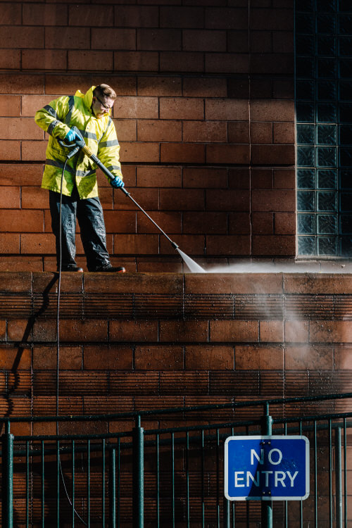 Workman sanitising and pressure-washing St Enoch Shopping Centre on the eve of the lockdown