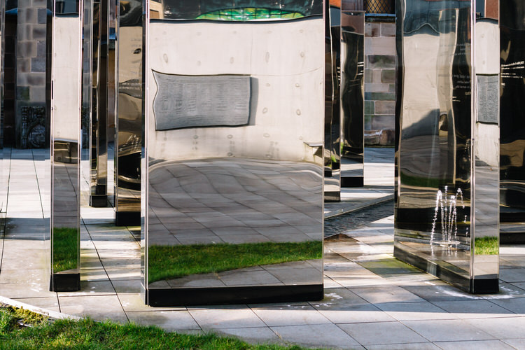 Mirrored surface reflecting the plaque with members of people who donated towards the creation of the memorial garden