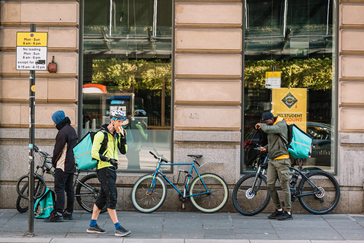 A flock of food delivery cyclists, some arriving, some waiting in a queue, some leaving