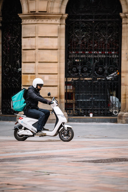 "Takeaway delivery scooter driver on the empty ""Style Mile"""