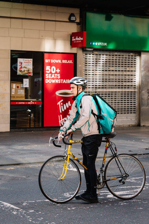 Deliveroo cyclist waiting at the traffic lights