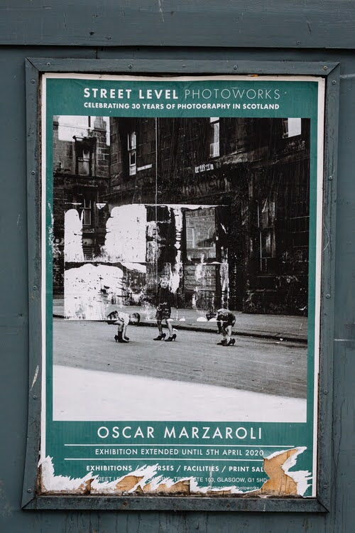 Three boys trying their mums shoes by Marzaroli on the pre-lockdown  Street Level Photoworks gallery poster