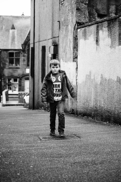 Urban portrait of a boy in a narrow alley