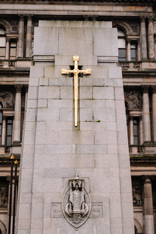 A gilded sword shaped like a cross over Glasgow coat of arms with St Mungo under a canopy on the obelisk